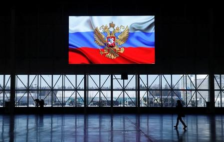 A view shows a screen displaying a flag with the Russian coat of arms during a news briefing near Moscow
