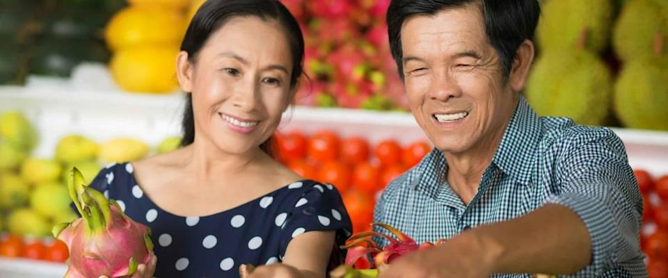 Close-up image of a senior couple buying fruits and vegetables in the market on the foreground