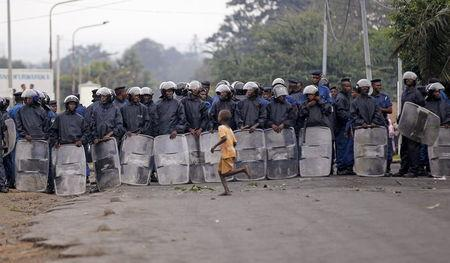 A child runs across a line of riot policemen standing in a formation as protestors gather and chant slogans in Bujumbura, Burundi April 30, 2015. REUTERS/Thomas Mukoya