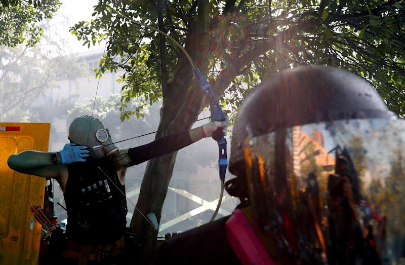 An anti-government protester uses a bow during clashes with police outside Hong Kong Polytechnic University (PolyU), in Hong Kong, China, Nov. 17, 2019. (Photo: Athit Perawongmetha/Reuters)