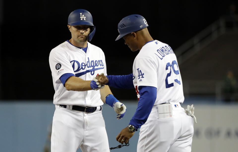 Los Angeles Dodgers' A.J. Pollock, left, shakes hands with first base coach George Lombard after hitting a bases-loaded single against the Arizona Diamondbacks during the third inning of a baseball game Friday, March 29, 2019, in Los Angeles. (AP Photo/Marcio Jose Sanchez)