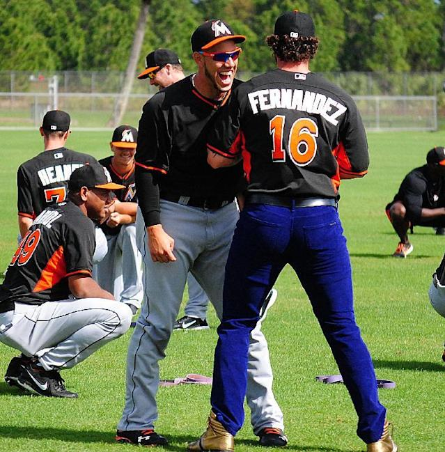 Miami Marlins catcher Jarrod Saltalamacchia, right, raided teammate Jose Fernandez's, left, locker and decided to wear Fernandez's jersey, purple jeans and gold high top sneakers to the team's morning stretch during a spring training baseball workout, Friday, March 7, 2014, in Jupiter, Fla. (AP Photo/Chuch King)