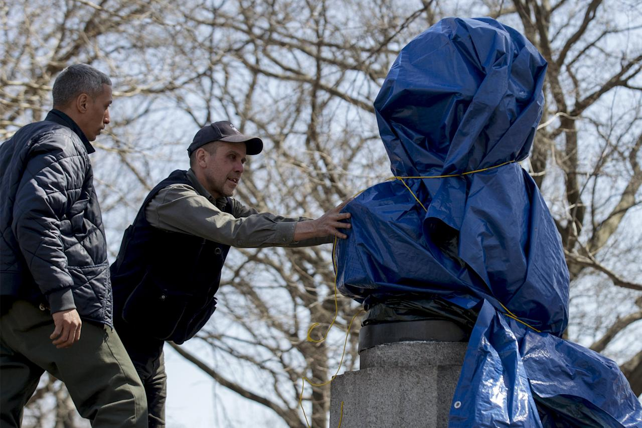 New York City Parks workers work to remove a covered large molded bust of Edward Snowden at Fort Greene Park in the Brooklyn borough of New York April 6, 2015. A group of anonymous artists erected a 4-foot-tall bronze statue of Edward Snowden, the former U.S. spy agency contractor famous for leaking classified information, in a New York City park overnight, officials said on Monday. REUTERS/Brendan McDermid