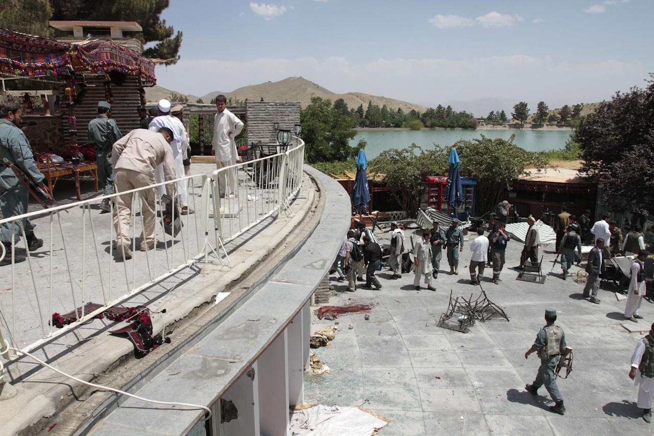 Afghan security forces and civilians are seen at the Spozhmai hotel on Lake Qurgha where security officials say Taliban insurgents have killed nearly two dozen people, most of them civilians, in an attack just north of Kabul, Afghanistan, Friday, June, 22, 2012. (AP Photo/Musadeq Sadeq)