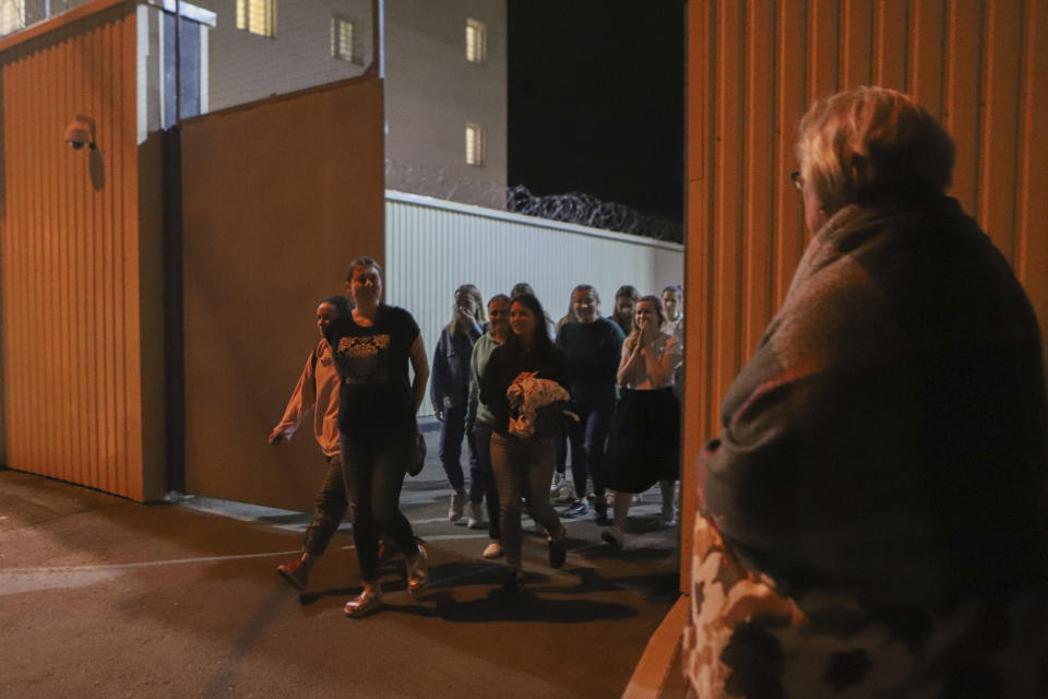 Women walk through a gate after being released from a detention center where protesters were detained during a mass rally following presidential election in Minsk, Belarus, Friday, Aug. 14, 2020. Nearly 7,000 people have been detained and hundreds injured in the clampdown on demonstrators protesting the official results that said Lukashenko won 80% of the vote and his top opposition challenger got only 10%. Police have broken up protests with stun grenades, tear gas, rubber bullets and severe beatings. (AP Photo)