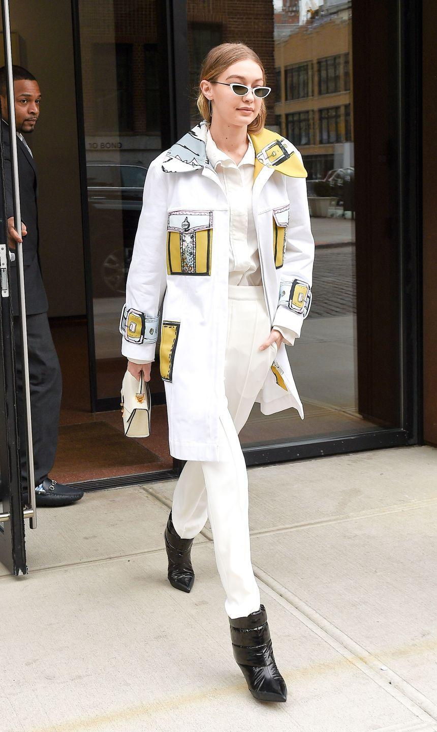 """<p>In a blue and yellow-accented white jacket, layered over a white collared button-down top and white pants, accessorized with pointed-toe black ankle boots, <a href=""""https://www.mytheresa.com/en-us/designers/linda-farrow/accessories.html?gclid=CjwKCAiAtorUBRBnEiwAfcp_YzN2qNN8D-Jdh8_rT_Zvx4X72gqLZIhnaTp9LBmIBRtEfVGksp5MOBoCgOUQAvD_BwE&ef_id=WmoiXAAAALIoCVHa:20180214020435:s"""" rel=""""nofollow noopener"""" target=""""_blank"""" data-ylk=""""slk:Linda Farrow sunglasses"""" class=""""link rapid-noclick-resp"""">Linda Farrow sunglasses</a>, and a white mini bag leaving her apartment building in NYC. </p>"""