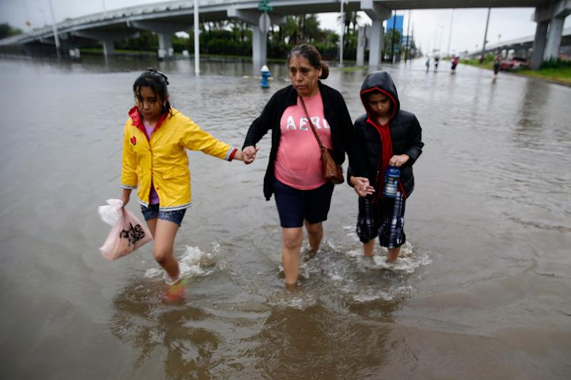 Ofelia Castro leads her grandchildren across a flooded street as they continue an hours long trek from their flooded house in the Edgewood area of South Houston to a relatives apartment miles away.