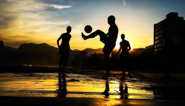 Children play football on Ipanema Beach in Rio de Janeiro during the 2014 World Cup. Hosts Brazil would suffer a humiliating 7-1 semi-final defeat to eventual winners Germany, while winless England failed to progress from the group stage of the tournament under Roy Hodgson (Mike Egerton/PA)