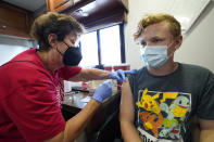 Nurse Carole Weaver, left, gives a COVID-19 vaccination shot to thirteen-year-old Jesse James, of Pleasantville, Iowa, Monday, Aug. 16, 2021, in Des Moines, Iowa. At the Iowa State Fair in Des Moines, where a million people are expected for the 11-day event, public health officials hope a vaccination station set up by pharmacists working for the Hy Vee food store chain will entice some of the vaccine-hesitant to get their shots. Visitors are packing in to state fairs in multiple Midwest states as COVID activity is increasing, raising concerns about the potential for rapidly accelerating spread of the delta variant of the COVID-19 virus. (AP Photo/Charlie Neibergall)