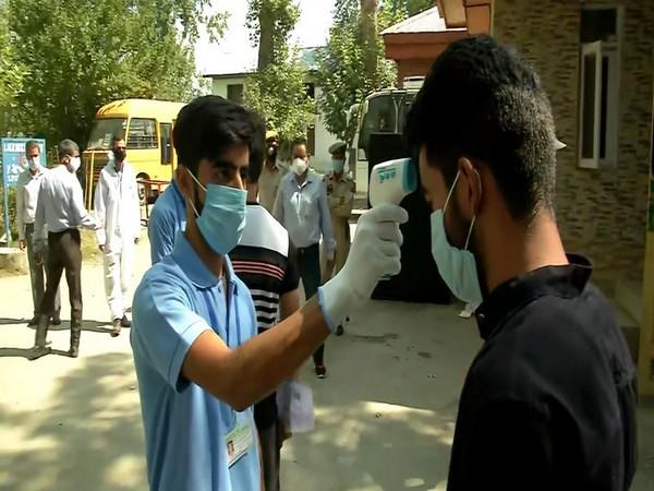 A NEET candidate getting his temperature checked before entering the examination centre. (Photo/ANI)