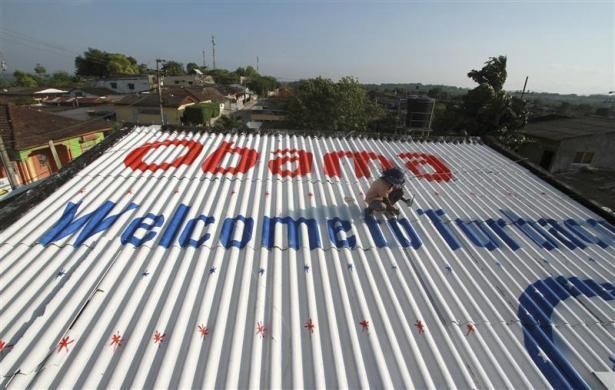 A painter working for Colombian attorney Silvio Carrasquilla paints the roof of Carrasquilla's house to welcome U.S. President Barack Obama in Turbaco, near Cartagena, April 11, 2012.