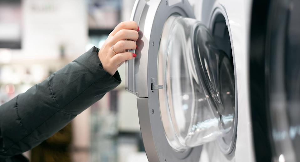 Pictured is a stock image of a hand opening a washing machine.