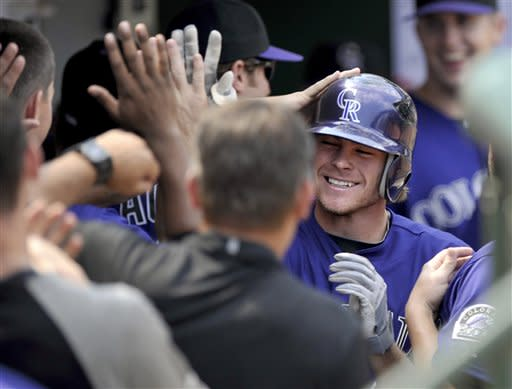 Colorado Rockies' Josh Rutledge celebrates with teammates in the dugout after hitting a two-run home run against the Chicago Cubs in the seventh inning of a baseball game in Chicago, Saturday, Aug. 25, 2012. Colorado won 4-3. (AP Photo/Paul Beaty)