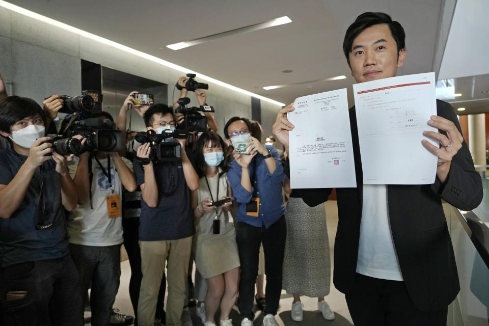 Lawmaker Cheng Chung-Tai displays a document as he is surrounded by reporters after being disqualified from the legislature in Hong Kong, Thursday, Aug. 26, 2021. Hong Kong authorities ousted Cheng from his seat Thursday after finding him to be insufficiently loyal amid Beijing's tightening grip on the semi-autonomous city. (AP Photo/Vincent Yu)