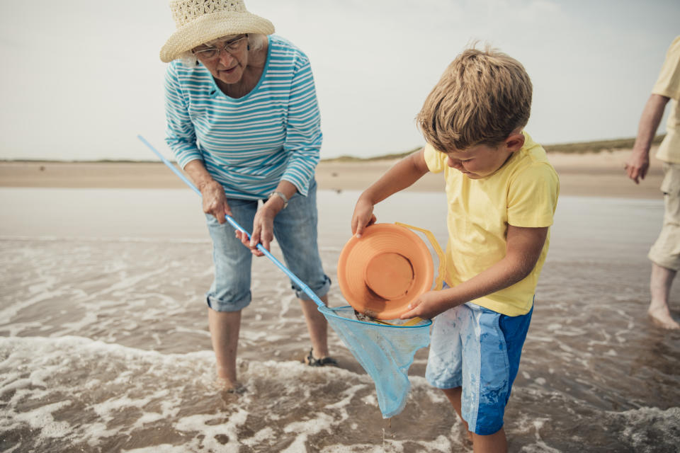 Searching for sea artifacts with a bucket and fishing rod at the beach with grandma.