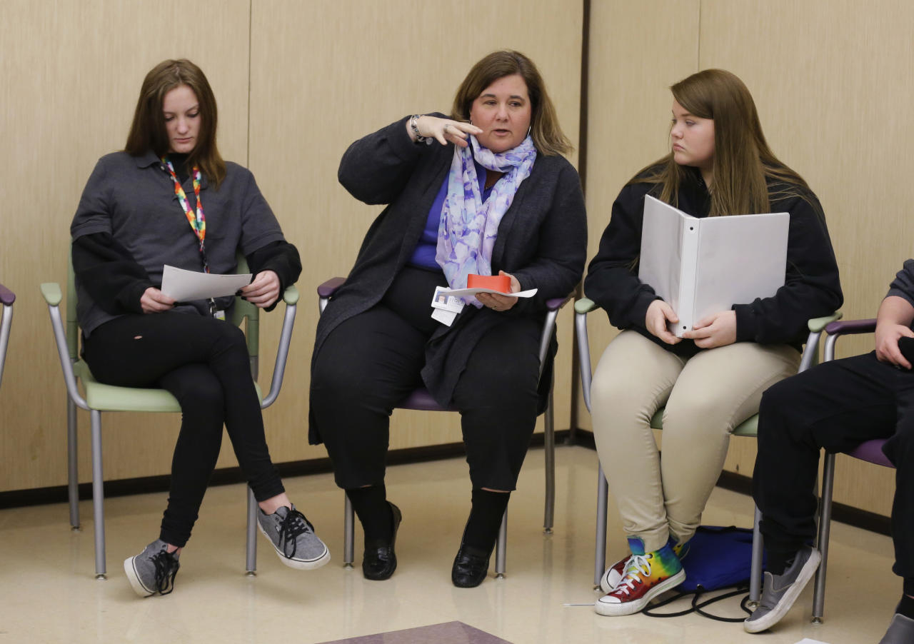 "In this Monday, March 13, 2017 photo, Rachelle Gardner, center, chief operating officer of Hope Academy and student Logan Snyder, right, lead an all-school meeting called ""circle"" before the start of classes in Indianapolis. For teenagers in treatment for addiction, returning to school means resisting offers to get high with old friends. Researchers said these kids do better at special ""recovery schools"" that use peer pressure in a different way, to support sobriety. (AP Photo/Michael Conroy)"
