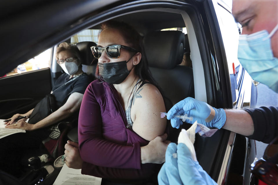 Caregiver Tracey Coker, center, and her mom Janis Coker receive their COVID-19 vaccinations from Newnan Fire Department firefighter/EMT Chase Taylor at the drive thru vaccination site in the Coweta County Fairgrounds, Thursday, Jan. 14, 2021, in Newnan, Ga. (Curtis Compton/Atlanta Journal-Constitution via AP)