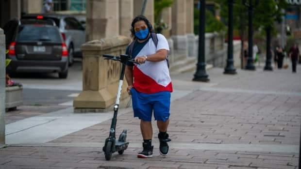 An e-scooter rider wears a mask during the COVID-19 pandemic while walking on a downtown Ottawa street. (Michel Aspirot/Radio-Canada - image credit)