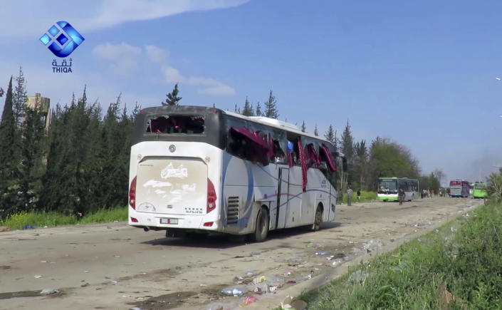This frame grab from video provided by the Thiqa News Agency, shows buses damaged by a blast at the Rashideen area, a rebel-controlled district outside Aleppo city, Syria, Saturday, April. 15, 2017. Syrian TV said at least 39 people were killed Saturday in an explosion that hit near buses carrying evacuees from two towns besieged by rebels nearby. (Thiqa News via AP)