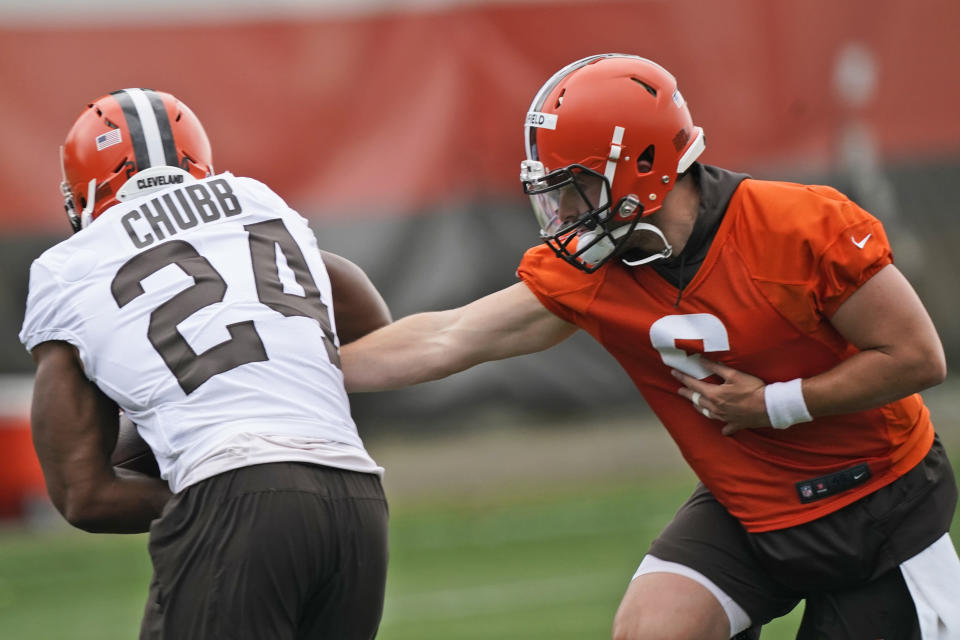 Cleveland Browns quarterback Baker Mayfield, right, hands the ball off to running back Nick Chubb during an NFL football practice, Thursday, July 29, 2021, in Berea, Ohio. (AP Photo/Tony Dejak)