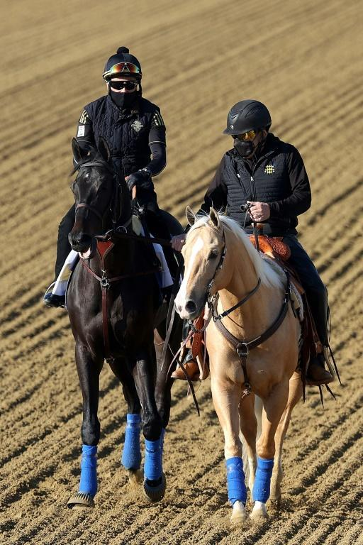 Kentucky Derby winner Medina Spirit, left, works Tuesday at Pimlico, where the Bob Baffert-trained colt will compete in Saturday's Preakness