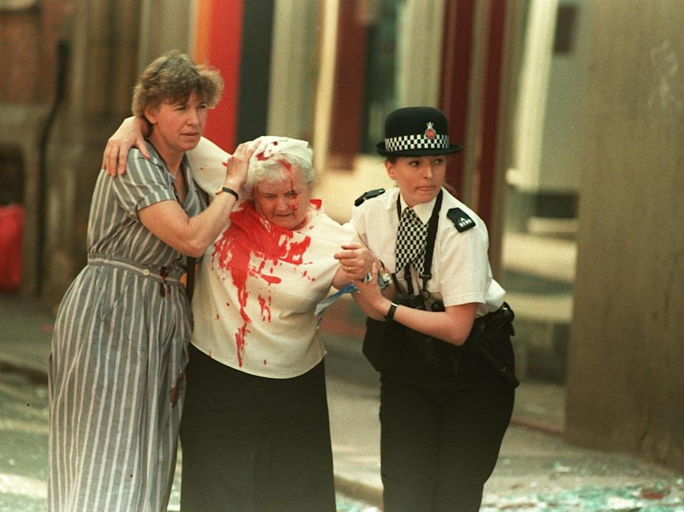 PC Vanessa Winstanley and another woman help a casualty away from the city centre (PA)