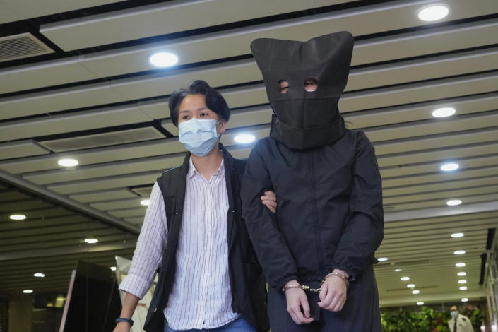 A hooded suspect is accompanied by a police officer to search evidence at an office in Hong Kong Thursday, July 22, 2021. Hong Kong's national security police on Thursday arrested five people from a trade union of the General Association of Hong Kong Speech Therapists on suspicion of conspiring to publish and distribute seditious material, in the latest arrests made amid a crackdown on dissent in the city. (AP Photo/Vincent Yu)