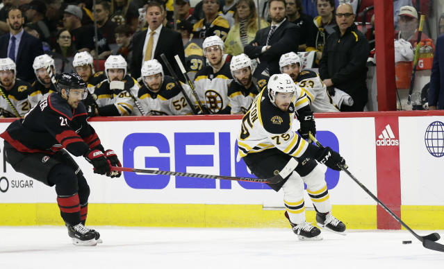 Boston Bruins' Connor Clifton controls the puck while Carolina Hurricanes' Nino Niederreiter (21), of Switzerland, defends during the first period in Game 3 of the NHL hockey Stanley Cup Eastern Conference final series in Raleigh, N.C., Tuesday, May 14, 2019. (AP Photo/Gerry Broome)