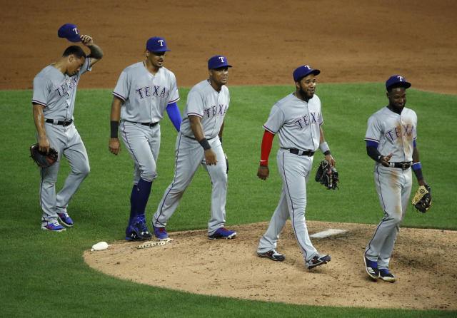 Players for the Texas Rangers walk off the field after their baseball game against the Kansas City Royals Monday, June 18, 2018, in Kansas City, Mo. The Rangers won 6-3. (AP Photo/Charlie Riedel)