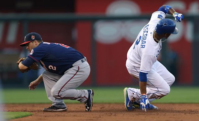 Kansas City Royals' Alcides Escobar (2) slides into second for a steal past Minnesota Twins second baseman Brian Dozier (2) in the third inning during a baseball game Wednesday, July 30, 2014, in Kansas City, Mo. (AP Photo/Ed Zurga)