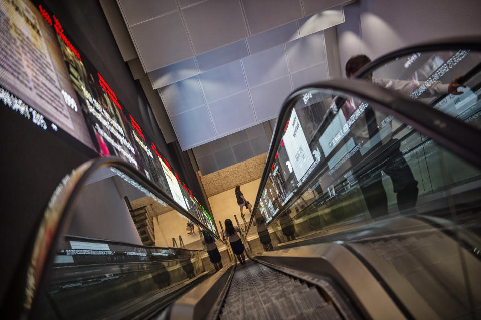 Pedestrians ride an escalator past an electronic screen and ticker board that indicates stock figures at the Singapore Exchange headquarters. (Photo: Getty Images)