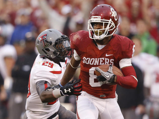 Oklahoma wide receiver Jalen Saunders (8) takes a Blake Bell pass past Texas Tech defensive back Olaoluwa Falemi (29) for a touchdown in the second quarter of an NCAA college football game in Norman, Okla., Saturday, Oct. 26, 2013. (AP Photo/Sue Ogrocki)