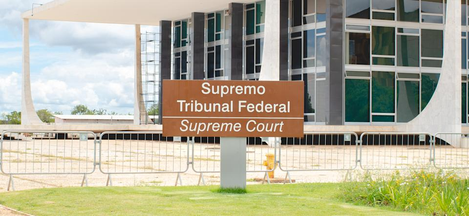 Photograph of the Federal Supreme Court in Brasilia, federal capital of Brazil.  Highlight the photo for a sculpture that represents justice. The STF was designed by Oscar Niemeyer and a sculpture of justice by the artist Alfredo Ceschiatti.