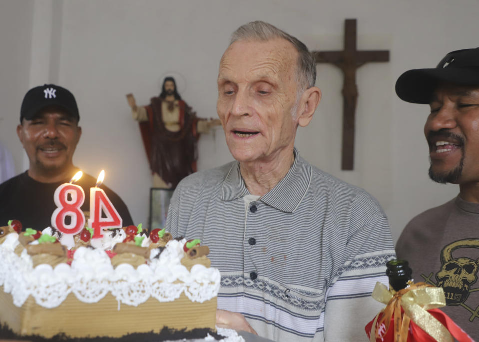 Now-defrocked Catholic priest Richard Daschbach, center, is presented a cake during his 84th birthday in Dili, East Timor, on Tuesday, Jan. 26, 2021. While he has his critics, Daschbach's support appears deep and widespread, extending beyond Oecusse to the capital, Dili. It includes members of the political elite, including former President Xanana Gusmao _ himself an independence hero _ who attended the opening of the trial in February, and this birthday celebration. (AP Photo/Ramundos Oki)
