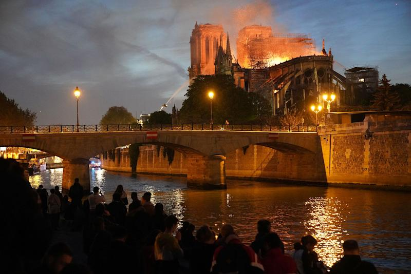 Bystanders watch as flames and smoke billow from the roof of the Notre Dame Cathedral in Paris on April 15, 2019.