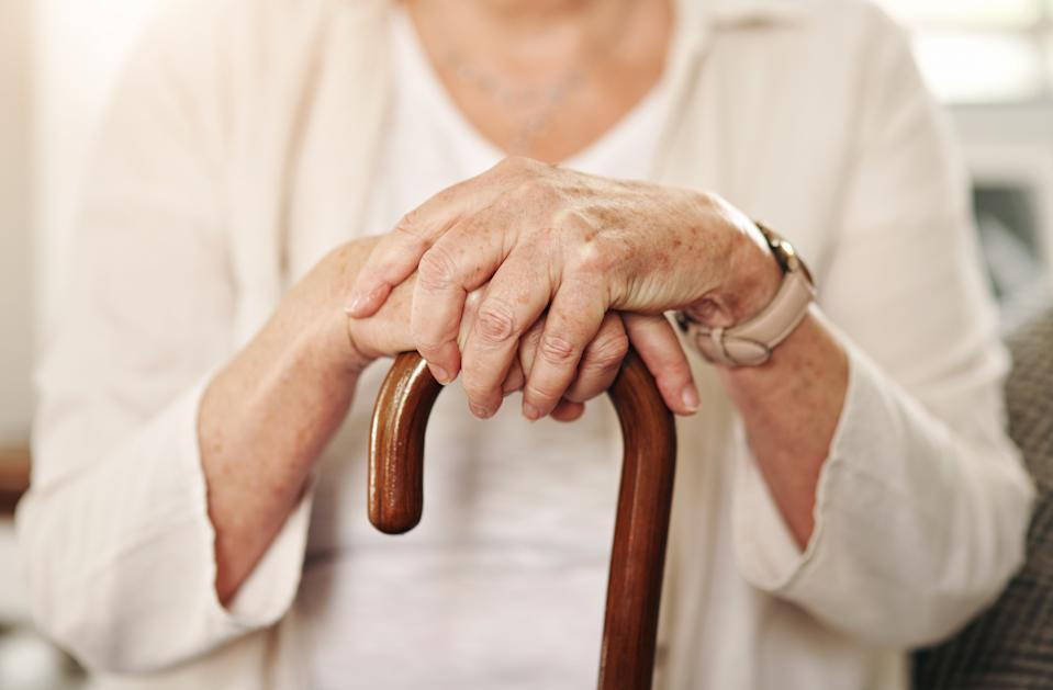 Cropped shot of a senior woman using a walking stick at home