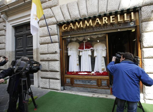TV crews film Gammarelli tailoring shop window where three sets of papal outfits - small, medium and large sizes - which will be sent to the Vatican for the new pope, are displayed, in Rome, Monday, March 4, 2013. For over a half century the Gammarelli family has produced the pope robes in three different sizes that are delivered before the conclave meets, in order to fit the newly elected popes. (AP Photo/Andrew Medichini)