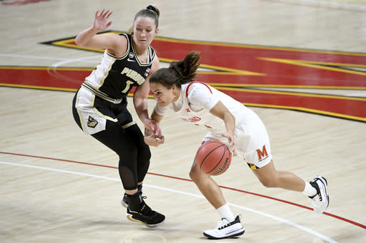 Maryland guard Katie Benzan (11) dribbles in front of Purdue guard Karissa McLaughlin (1) during the second half of an NCAA college basketball game, Sunday, Jan. 10, 2021, in College Park, Md. (AP Photo/Will Newton)