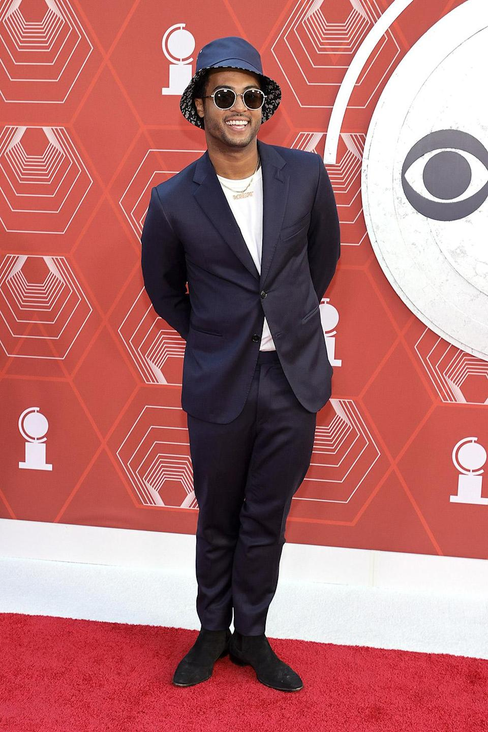 <p>Bobby Wooten III wears a navy suit, matching bucket hat and sunglass on the red carpet. </p>