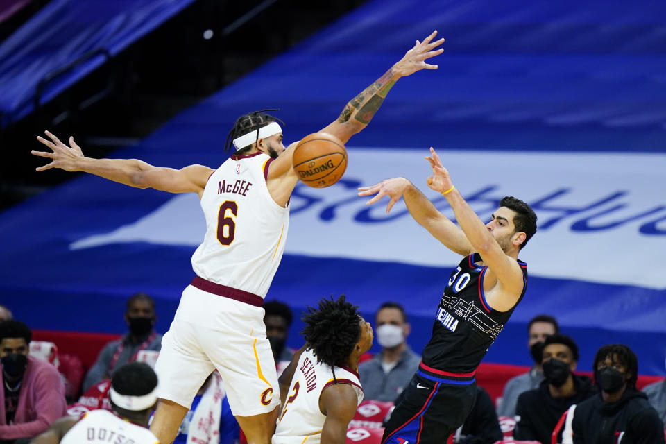 Philadelphia 76ers' Furkan Korkmaz, right, passes the ball against Cleveland Cavaliers' JaVale McGee during the first half of an NBA basketball game, Saturday, Feb. 27, 2021, in Philadelphia. (AP Photo/Matt Slocum)