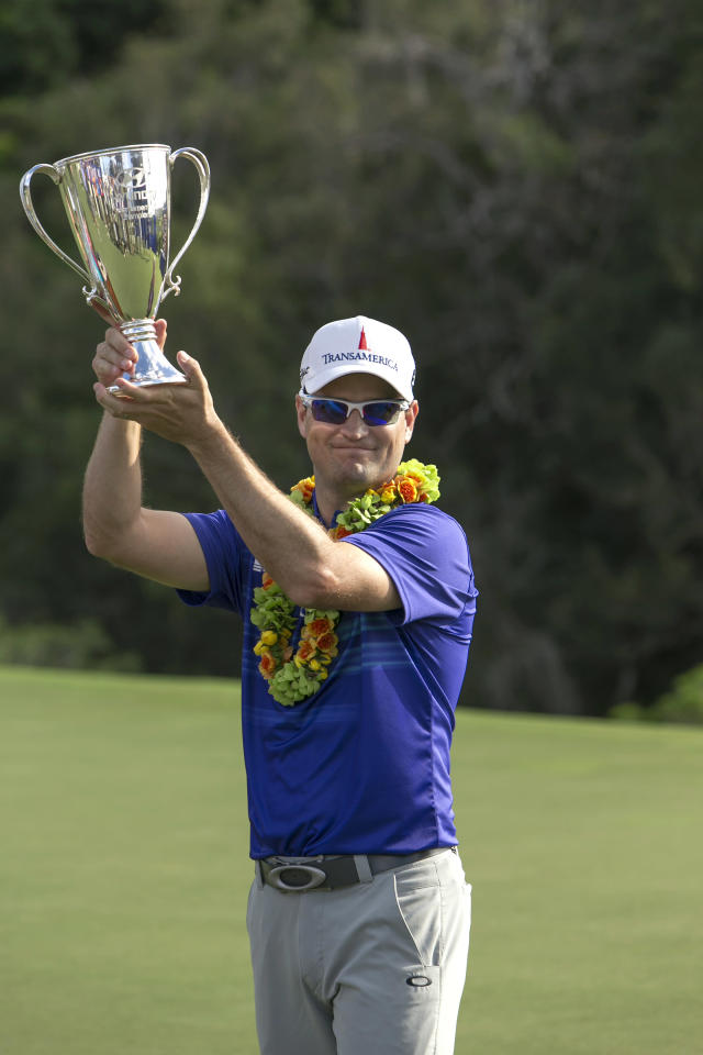 Zach Johnson holds the first place trophy after winning the Tournament of Champions golf tournament, Monday, Jan. 6, 2014, in Kapalua, Hawaii. Johnson pulled away with three straight birdies on the back nine at Kapalua and closed with a 7-under 66 for a one-shot victory over Jordan Spieth on Monday. (AP Photo/Marco Garcia)