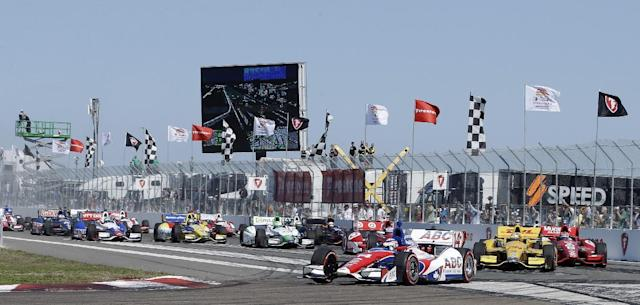 Takuma Sato, (14), of Japan, leads the field into the first turn at the start of the IndyCar Series auto race, Sunday, March 30, 2014, in St. Petersburg, Fla. (AP Photo/Chris O'Meara)