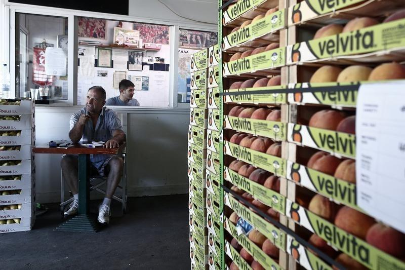 An employee sits next to crates of peaches at the central vegetable market in Athens