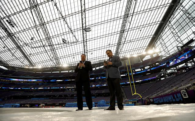 Men looking at their phones stand beneath the transparent roof of US Bank Stadium during a media preview for this weekend's Super Bowl in downtown Minneapolis, Minnesota, U.S. January 30, 2018. REUTERS/Kevin Lamarque