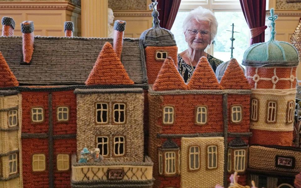 Margaret Seaman with her incredible piece of work, which even features miniature woollen versions of the Queen and the Duke of Edinburgh on a balcony - PA