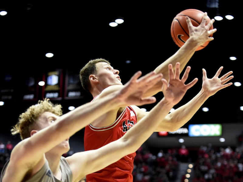 San Diego State forward Yanni Wetzell (5), right, grabs a rebound in front of Nevada forward Zane Meeks (15) during the second half of an NCAA college basketball game Saturday, Jan. 18, 2020, in San Diego. (AP Photo/Denis Poroy)