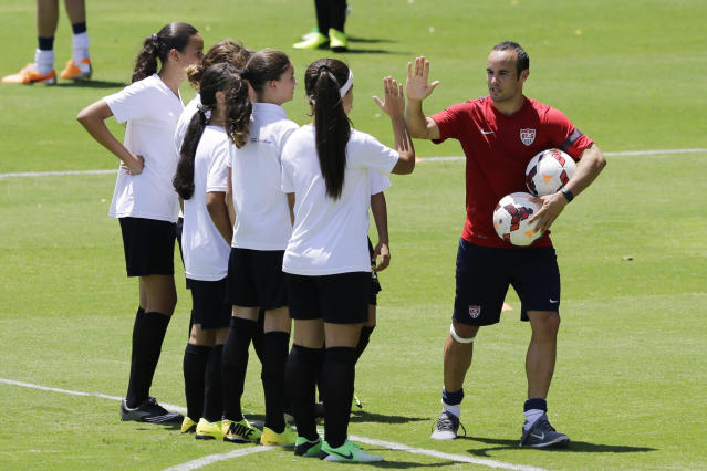 """United States' Landon Donovan high fives young players who will attend a program coined """"Sports for All', organized by the US consulate to give public school kids soccer and English lessons, in Sao Paulo, Brazil, Wednesday, Jan. 22, 2014. The US national soccer team is training in Sao Paulo to prepare for the World Cup tournament, which gets underway in June. (AP Photo/Nelson Antoine)"""
