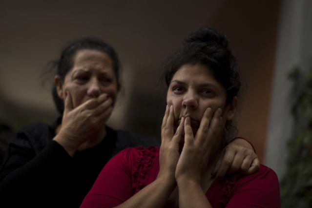 <p>Raquel de Cadiz Escudero, 30, right, and her mother-in-law, Carmen Escudero Garcia, 59, wait for the police to evict Raquel's family in Madrid, May 19, 2014. (AP Photo/Andres Kudacki) </p>