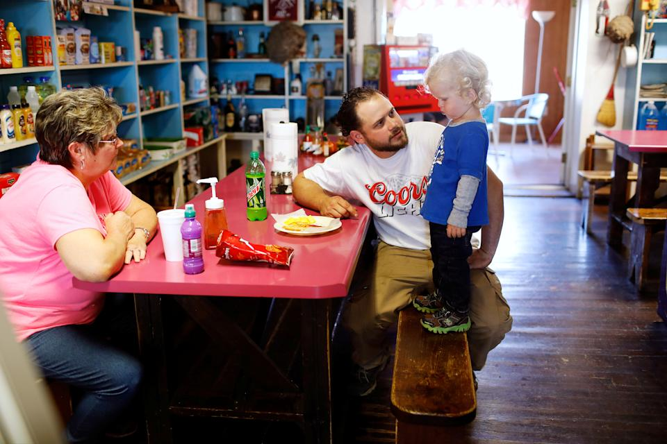 Employee Joyce Chandler (L) looks on as Antonin Bohac, who works at a lead mine for The Doe Run Company, encourages his 2-year-old son, Sawyer to eat while dining at the Bixby Country Store in Bixby, Missouri, U.S. November 17, 2016.  Picture taken November 17, 2016. To match Special Report USA-LEAD/TESTING    REUTERS/Whitney Curtis