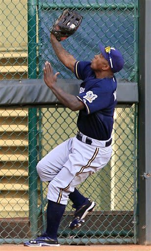 Milwaukee Brewers center fielder Nyjer Morgan catches a fly ball hit by Cincinnati Reds' Zack Cozart in the third inning of a baseball game, Tuesday, June 26, 2012, in Cincinnati. (AP Photo/Al Behrman)